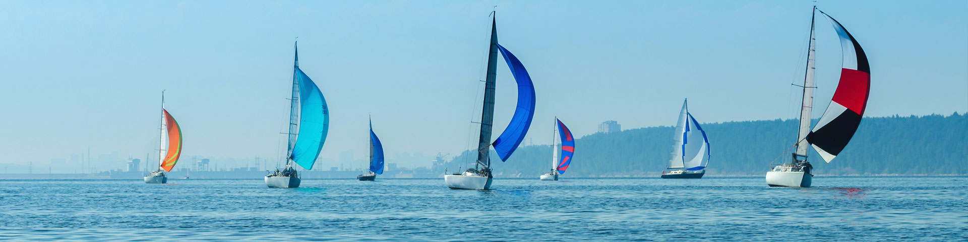 Syv forskellige sejlbåde med blå himmel på vandet