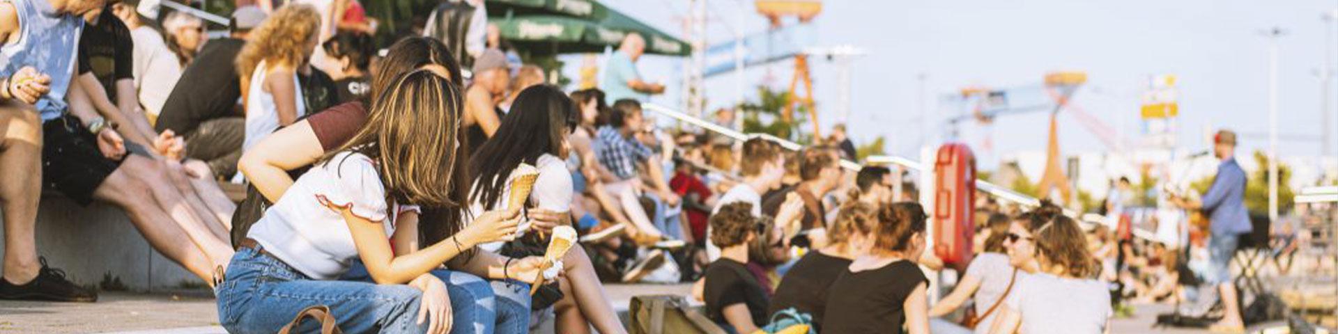 Eventkalender - Mennesker er på koncert, sidder i solen og nyder atmosfæren