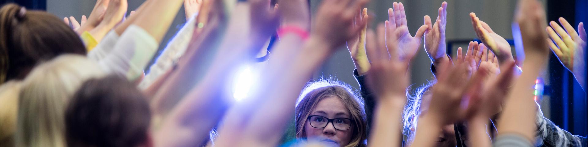 unge mennesker som holder hænderne op