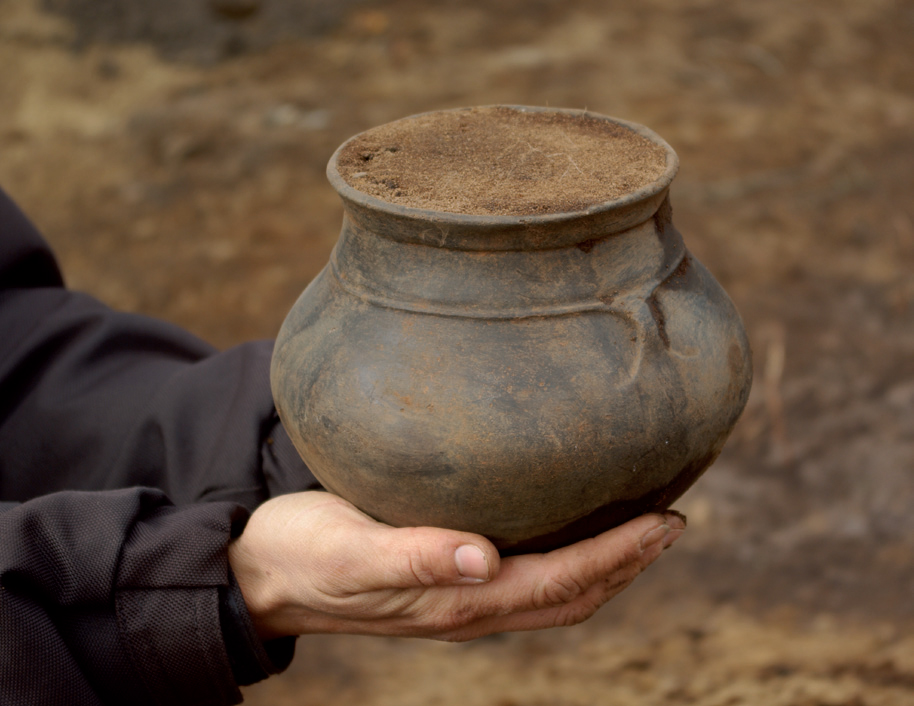 Arkæologen viser en flot, hel urne frem.