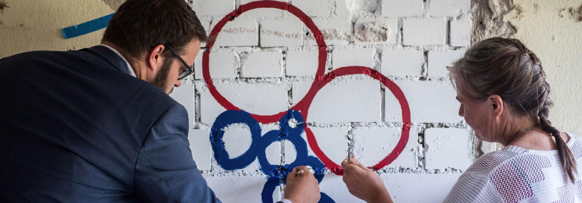 Headerbild: 2 Personen - ein Mann und eine Frau - malen mit Farbe und Pinsel das Interreg Logo an eine Mauerwand.