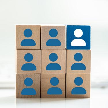 9 Holzklötze mit blauen Figur-Icons, der Klotz oben rechts ist blau und die Figur weiß