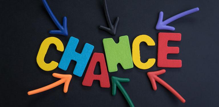 Das Wort Chance bunt vor schwarzem Hintergrund, 6 bunte Pfeile zeigen in Richtung des Wortes