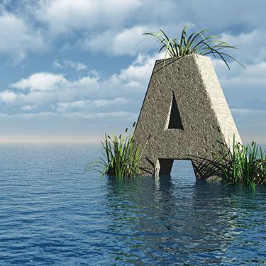 Der Buchstabe A als großer Stein mit Grasbüscheln, steht im Wasser bei leicht bewölktem Himmel