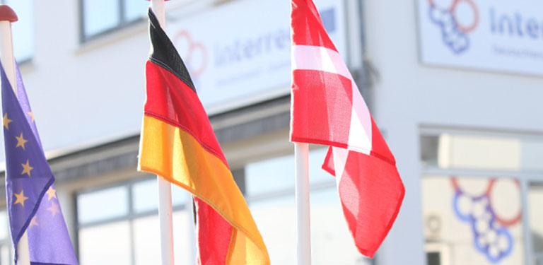 Interreg-Gebäude im Hintergrund, davor wehen die europäische, deutsche und dänische Flagge