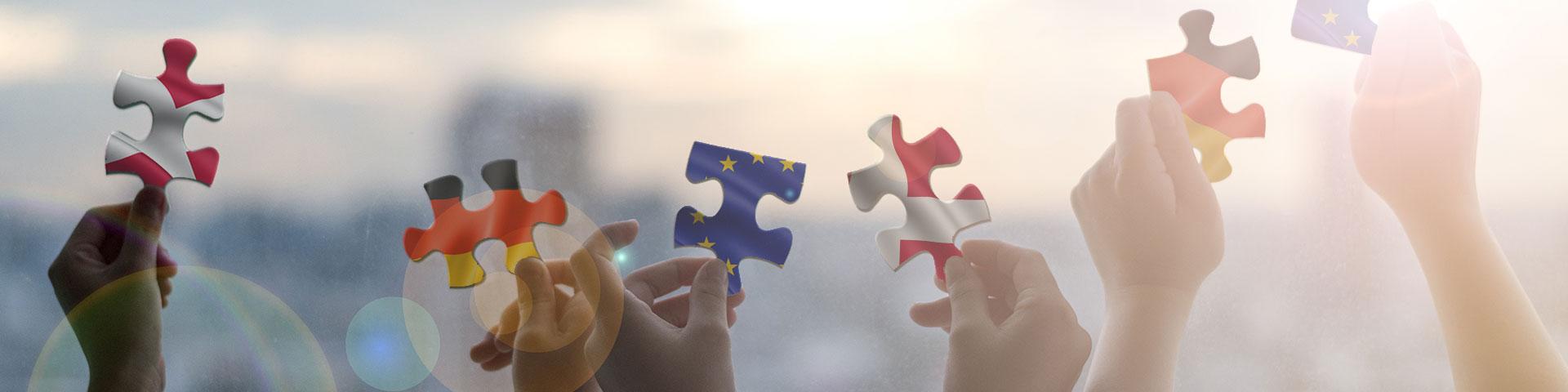 Hände halten Puzzleteile hoch die entweder die europäische, dänische oder deutsche Flagge abbilden