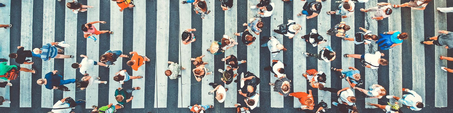 Vogelperspektive eines Zebrastreifens mit vielen Menschen die die Strasse überqueren