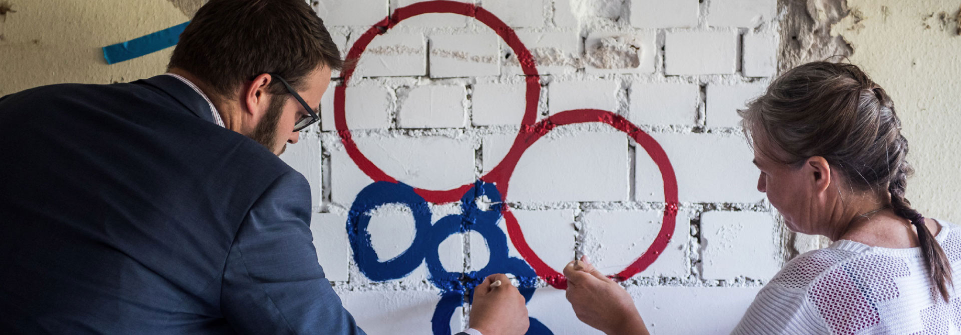 Interreg 5a - Zusammen sind wir Mehrwert. Zwei Projektleiter zeichnen das Interreg-Logo. Link zur Projektübersicht.