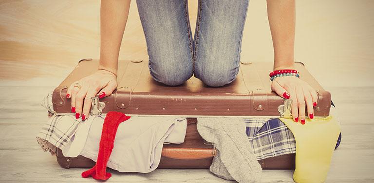 Koffer aus dem Klamotten quillen, Person kniet drauf