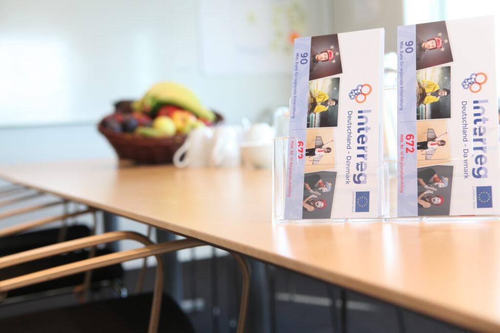 Tisch auf dem Flyer von Interreg zu sehen sind