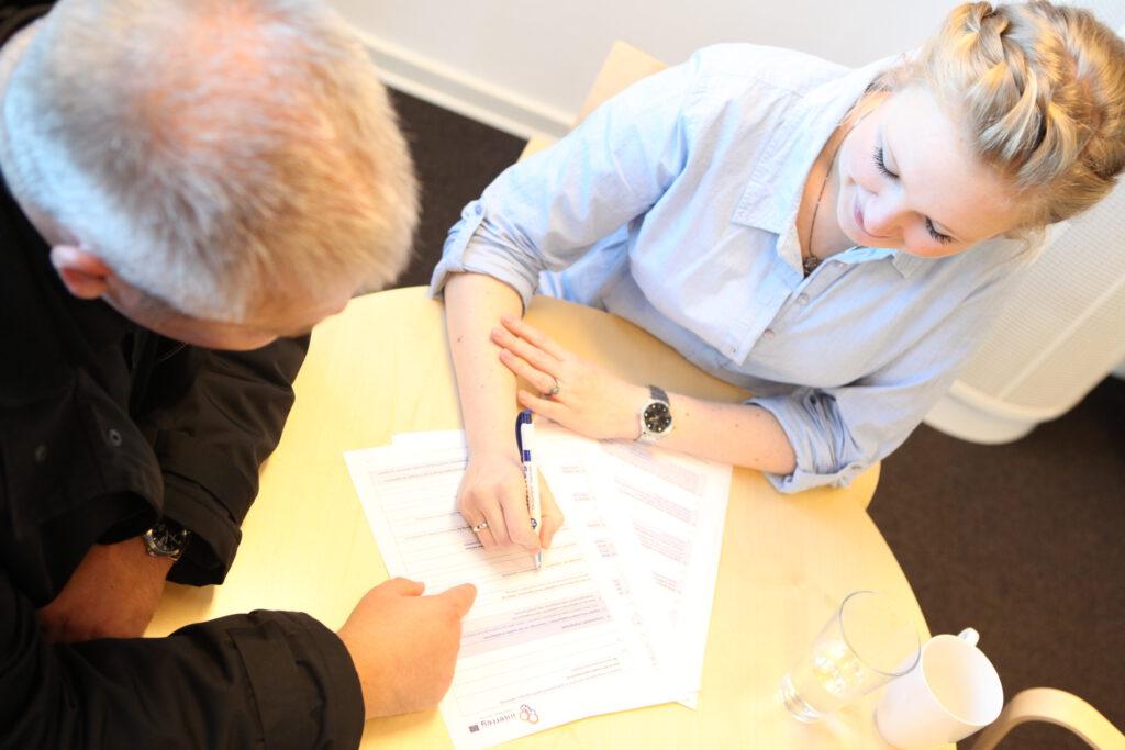 Zwei Menschen sitzen über Dokumenten