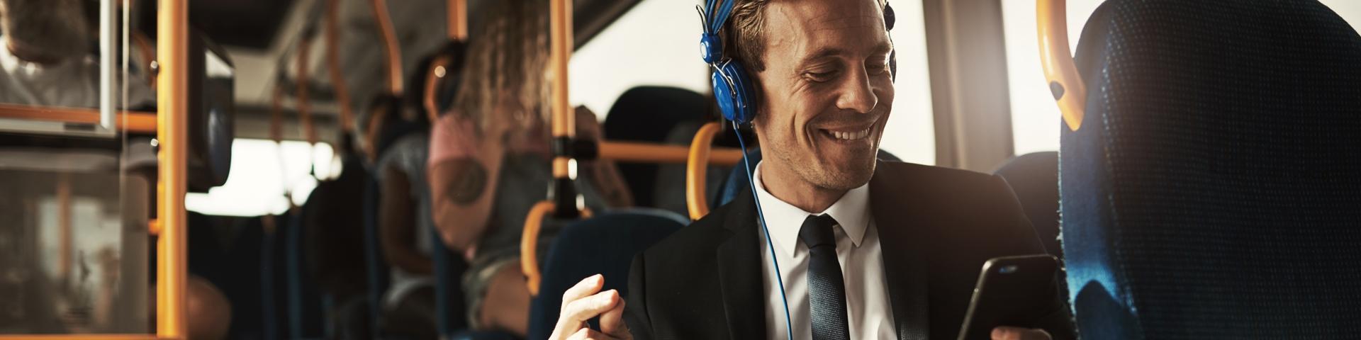 Titelbild für Priorität 3 - Arbeitsmarkt, Beschäftigung und Ausbildung - Junger Mann sitzt im Bus, hat blaue Kopfhörer auf und lächelt während er auf sein Handy guckt.