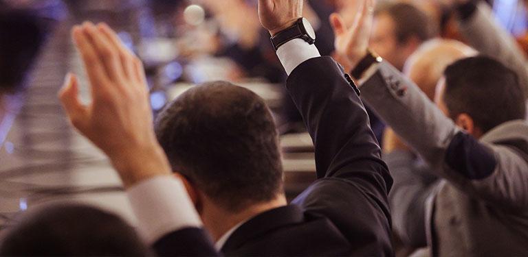 Menschen bei einem Meeting stimmen ab