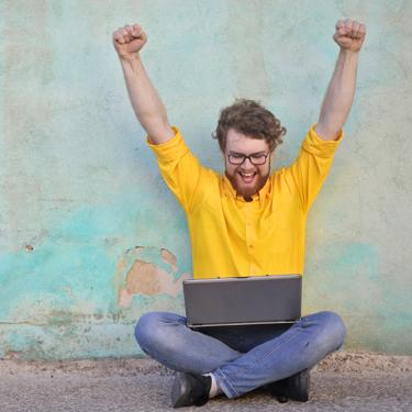 Mann im gelben Hemd sitzt im Schneidersitz mit einem Laptop auf dem Schoß, streckt die Arme nach oben und freut sich