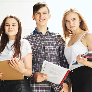 Ein Junge und zwei Mädchen mit Büchern und Heften in der Hand