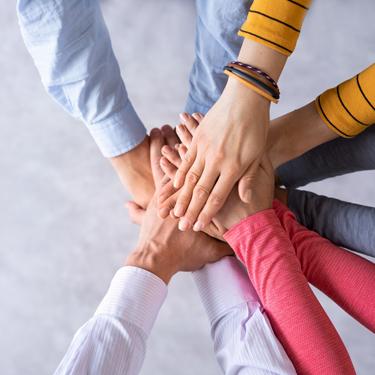 5 paar Hände liegen übereinander