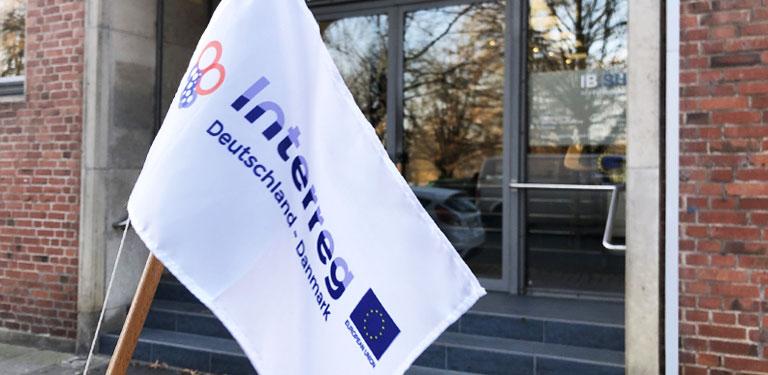 Vor dem Gebäudeeingang weht die Interregflagge