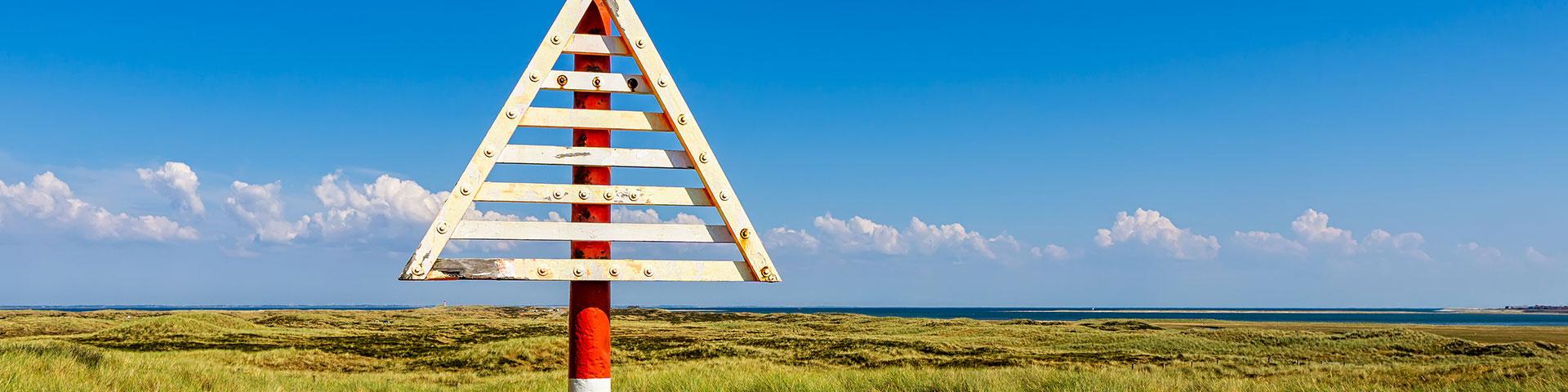 Dreieck aus Holz an roter Stange auf flachem Land vor blauem Himmel und dem Meer