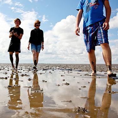 3 Menschen stehen im Watt vor leicht bewölktem Himmel