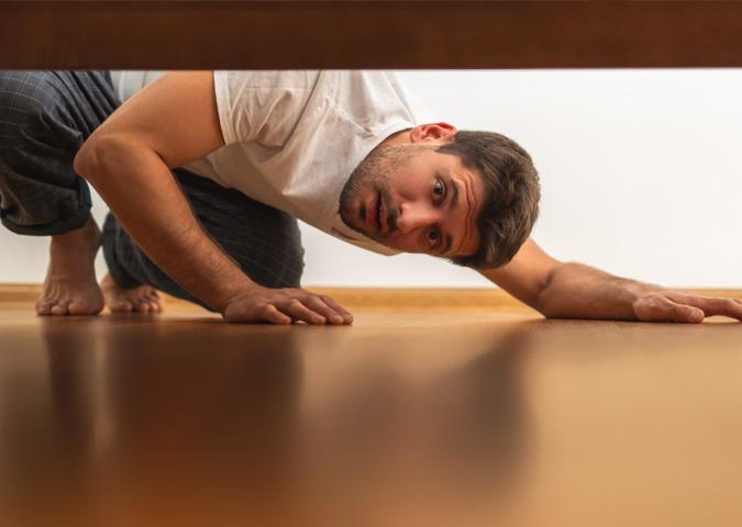Mann guckt unters Bett