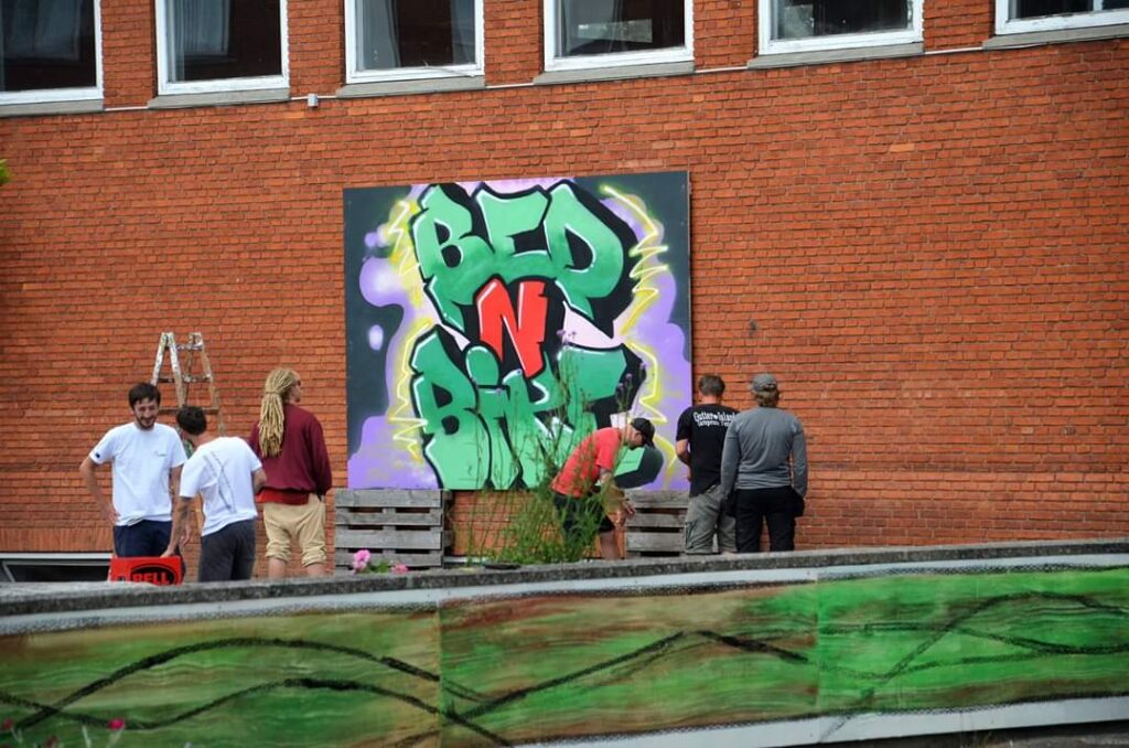 Menschen vor großer Grafittiwand