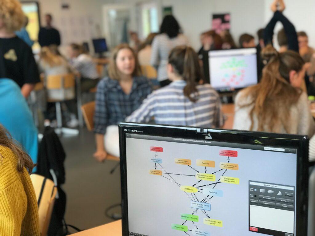 Jugendliche unterhalten sich in Gruppen im Klassenzimmer