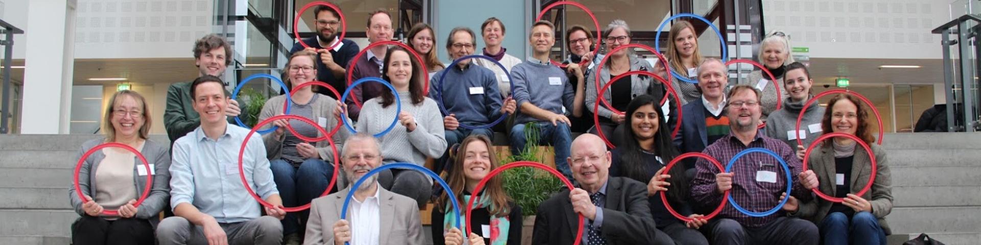 Gruppenfoto, Personen halten rote und blaue Ringe hoch