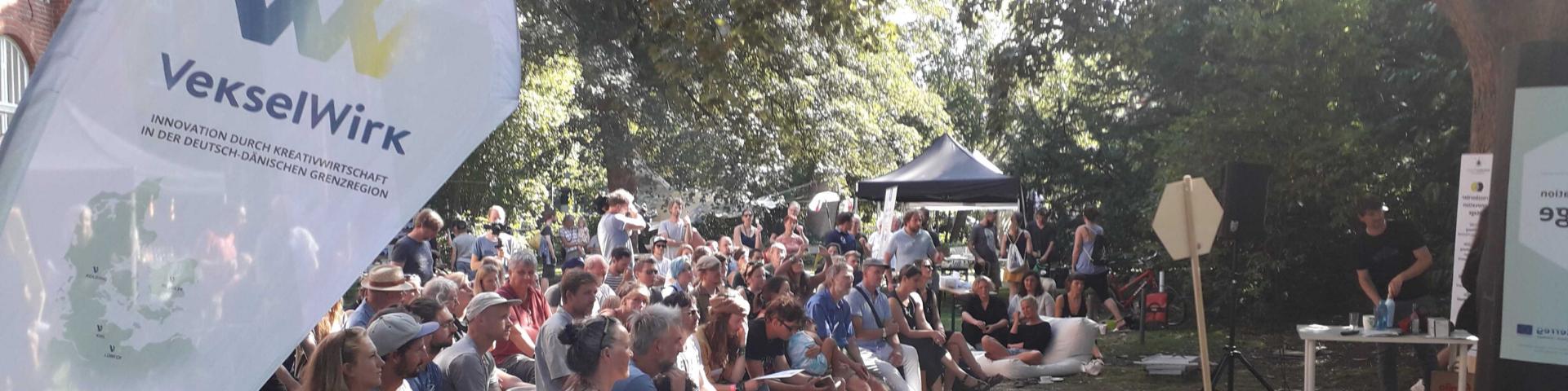 Menschen draussen im Park sitzen zusammen