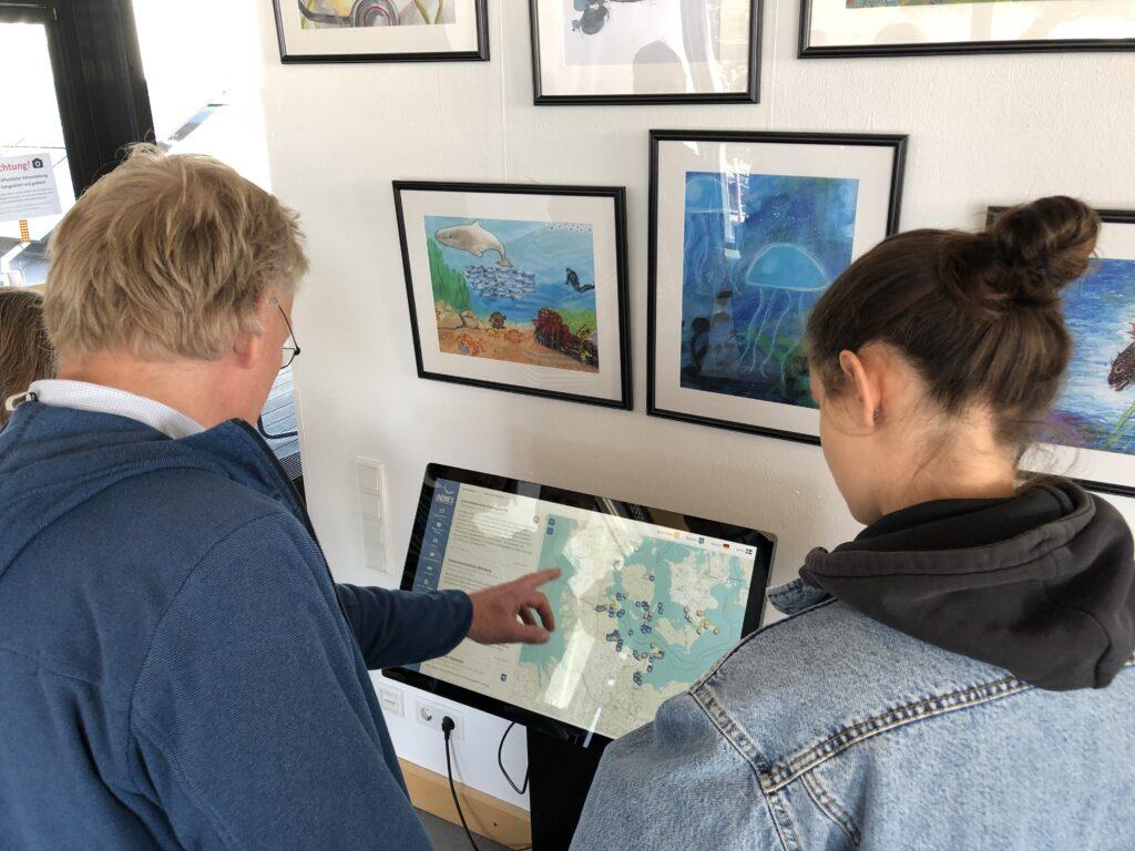 Zwei Menschen gucken auf digitale Karte
