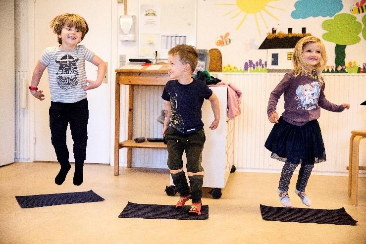 Kinder spielen und bewegen sich zur Musik