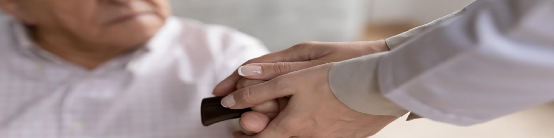 Frau hält älterem Mann Hand